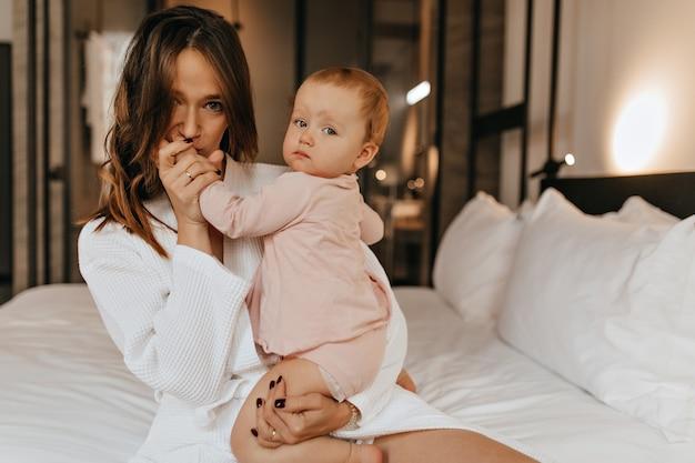 バスローブを着た緑色の目の女性が子供の手にキスをします。ママと娘はベッドに座って自宅でポーズします。