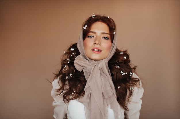 白いブラウスと髪のポーズで小さな花を持つ緑色の目の女性。スカーフの女性がカメラを見ています。