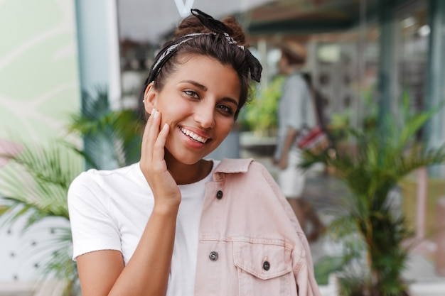 흰색 티셔츠와 백설 공주의 미소를 지닌 분홍색 재킷에 녹색 눈을 가진 여자가 거리에서 포즈를 취하고 앞을 본다.