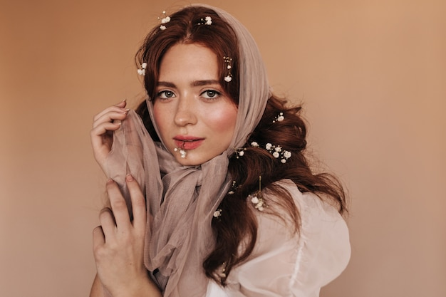 Green-eyed woman in light outfit coquettely looks at camera on beige background, playing with scarf.
