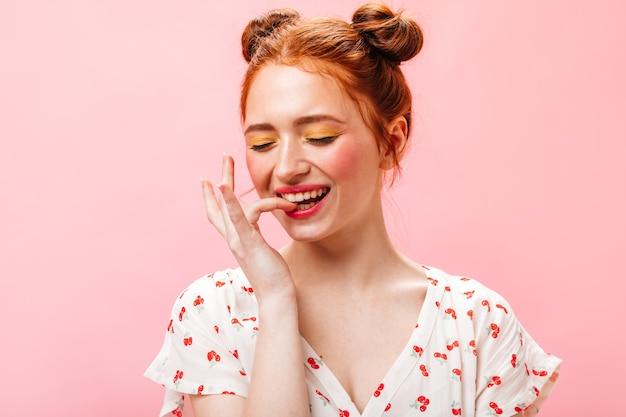 緑色の目の女性はピンクの背景に優しく微笑む。黄色のアイシャドウを持つ赤毛の女性の肖像画。