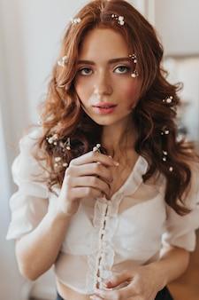 ウェーブのかかった髪の花を持つ緑色の目の女性がカメラをのぞきます。白いブラウスの女性のスナップショット。
