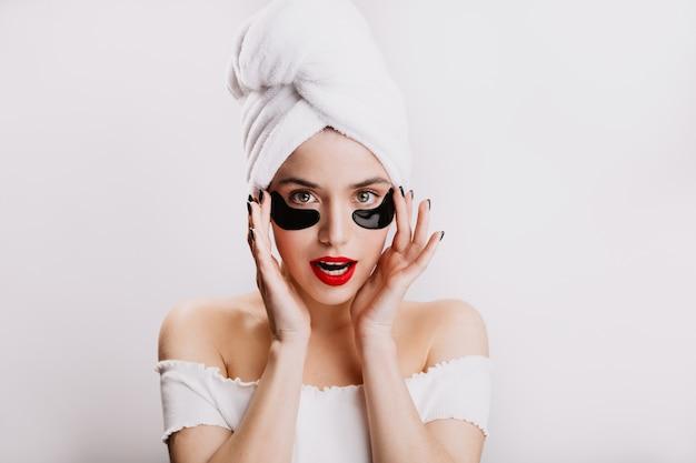 빨간 립스틱을 가진 green-eyed 여자는 눈 밑의 피부를 돌 봅니다. 흰 벽에 샤워 후 모델의 초상화입니다.