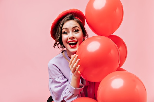 Donna dagli occhi verdi con rossetto rosso ride e pone con palloncini su sfondo isolato.