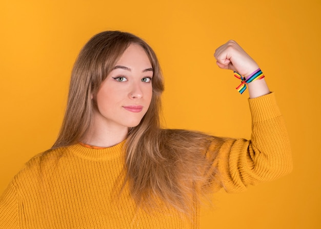 Green eyes blonde girl, with raised hand with raised rainbow bracelet, lgbt, gay pride, on pastel yellow background