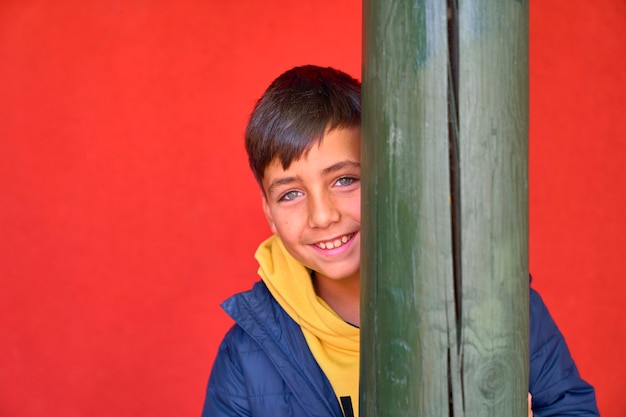 Green eyes kid with red background smiling