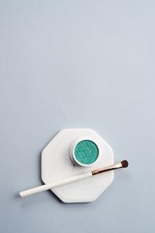 緑のアイシャドウと化粧ブラシ
