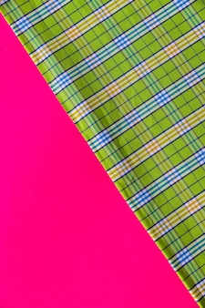 Green fabric material on pink background