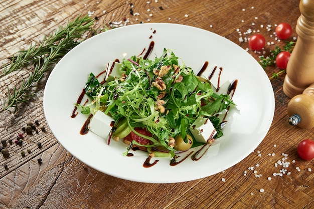 Green farm salad with lettuce, fresh vegetables, sweet onions and feta cheese in a white bowl on a wooden surface in a composition with spices