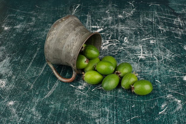 Green feijoa fruits falling out from the vase on marble surface.