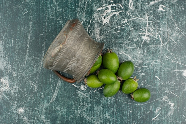 Green feijoa fruits falling out of the vase on marble surface.