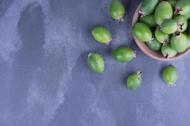 Зеленые плоды фейхоа в деревянной чашке на синем столе.