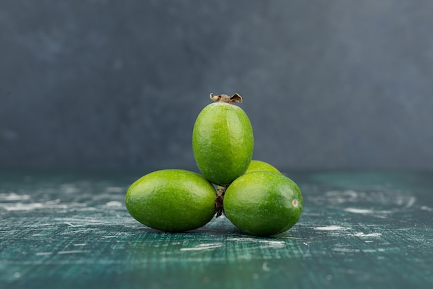 Green feijoa fruits on marble surface