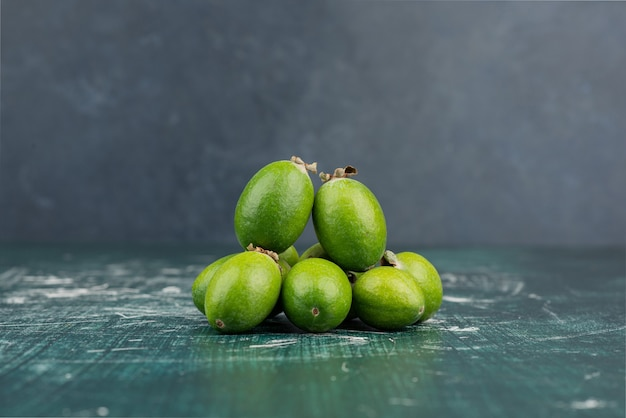 Green feijoa fruits on marble surface.