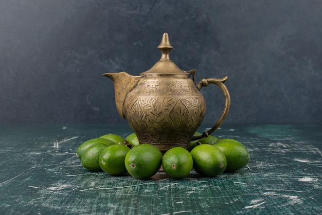 Green feijoa fruits on marble table with classic teapot