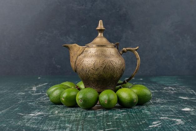 古典的なティーポットと大理石のテーブルの上の緑のフェイジョアフルーツ