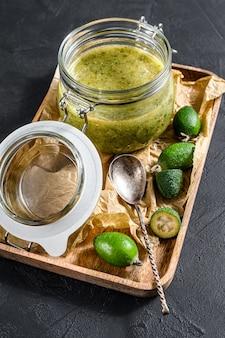 ガラスの瓶に木製のまな板に緑のフェイジョアジャム。自然な自家製デザート。黒の背景。上面図