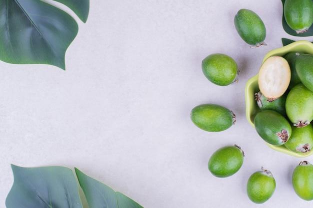 Feijoas verdi in una tazza con foglie intorno.