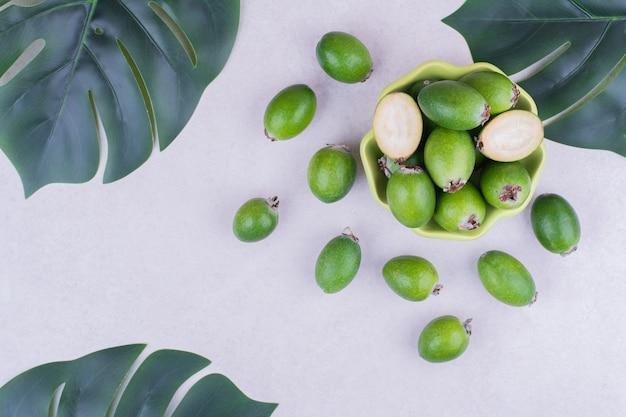 Feijoas verdi in una tazza verde con foglie intorno
