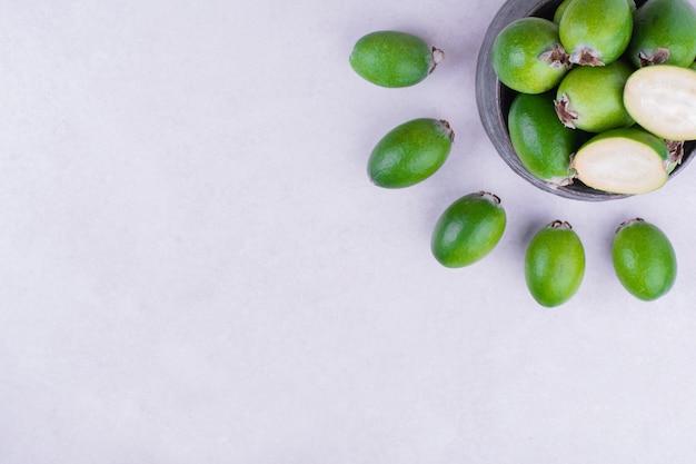 회색에 금속 냄비에 녹색 feijoas.