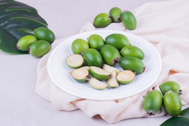 Зеленые фейхоа в белой тарелке с листьями вокруг