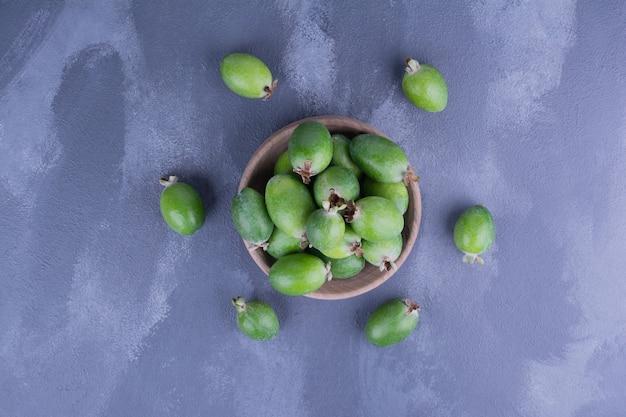 파랑에 나무 컵에 녹색 feijoas.