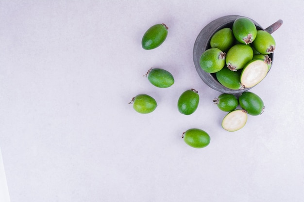 Feijoas verdi in un vaso metallico su superficie bianca
