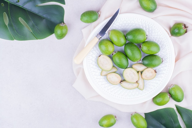 Feijoas verdi in un piatto bianco con foglie intorno