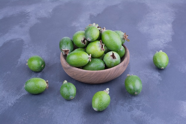 Feijoas verdi in una tazza di legno sulla superficie blu