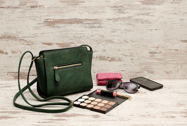 Green female bag, phone, eyeshadow palette, phone, sunglasses and lipstick on a wooden