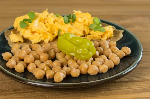 Green fermented green peppers and chickpeas. scrambled eggs on pita bread. light wooden background