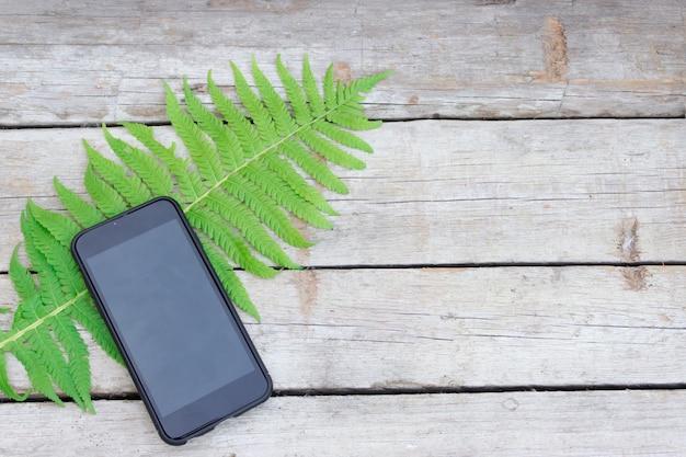 녹색 고비 잎 검은 휴대 전화는 나무 테이블에 놓여