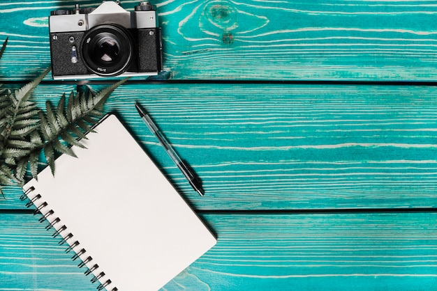 Green fern leaves; spiral notepad; pen and camera against wooden turquoise background