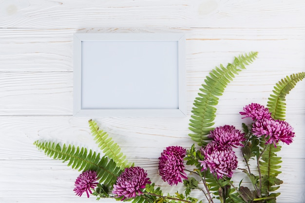 Green fern leaves with purple flowers and frame on table