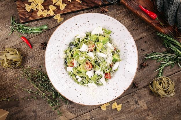トマトとチーズの木製のテーブルとグリーンフェットチーネパスタ