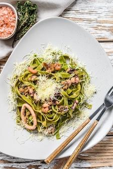 Паста со шпинатом green fettuccine с морепродуктами в сливочном соусе. белый фон. вид сверху.