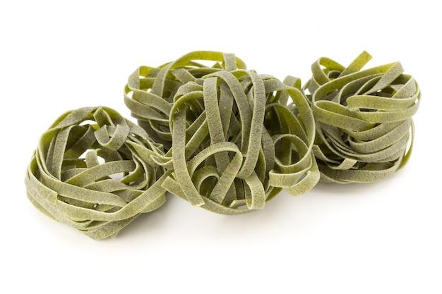 Green fettucine pasta on white
