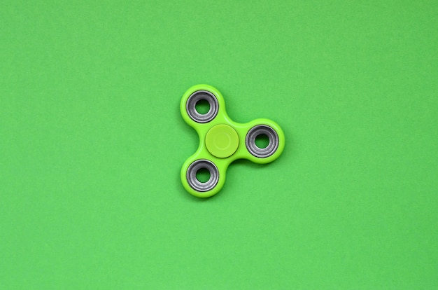 Green fidget spinner lies on texture background
