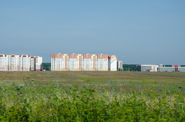 Green field and looking to new residential buildings. real estate, choosing home or renting property at summer