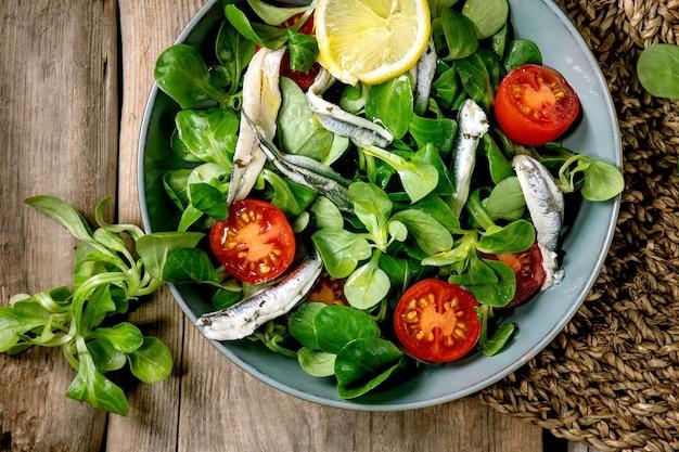 アンチョビのピクルスまたはイワシの切り身とチェリートマトのグリーンフィールドサラダ、古い木の表面のストローナプキンにレモンとオリーブオイルを添えた青いボウルで提供 Premium写真