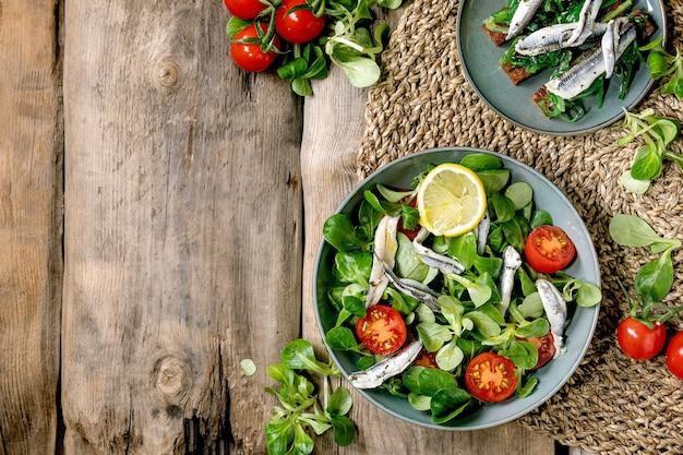 アンチョビまたはイワシの切り身のピクルスとチェリートマトのグリーンフィールドサラダ、レモンとオリーブオイルを添えた青いボウルでお召し上がりいただけます