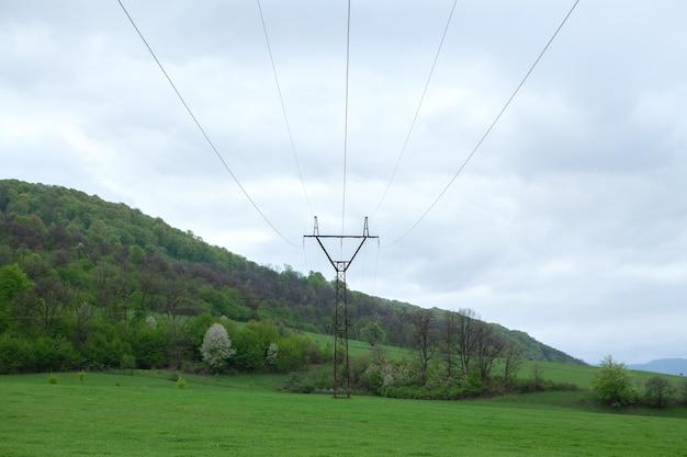 夕方の緑の野原と高電圧の電気塔