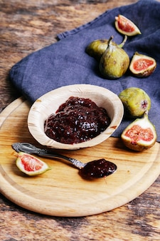 Green fig with jam on rustic table