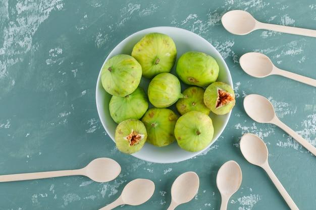木製のスプーンで皿に緑のイチジクを石膏の壁に平らに置く