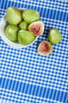 白いボウルと青いテーブルクロスの緑のイチジク