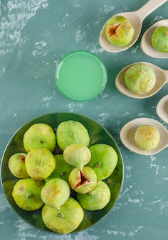 Зеленые фиги в деревянных ложках и тарелке с видом сверху напитка на гипсовой стене