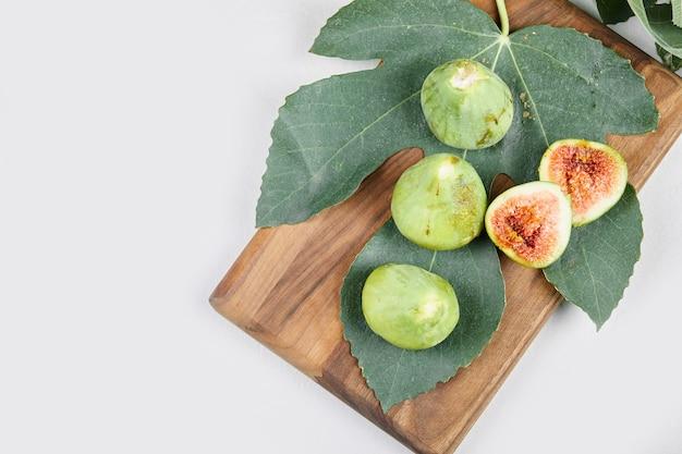 Зеленый инжир, изолированные с зелеными листьями.