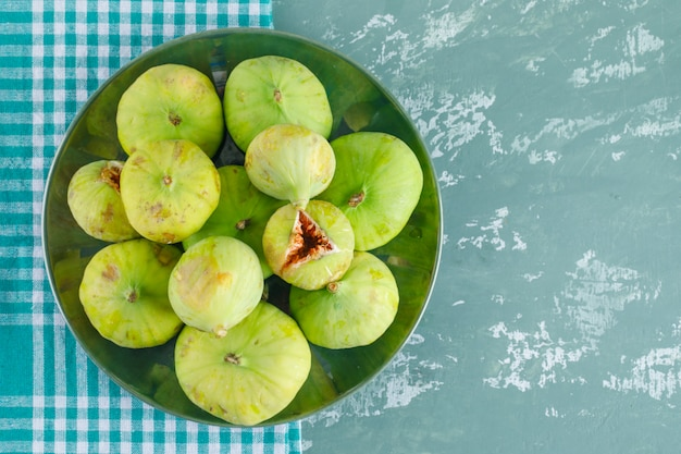 Green figs in a plate on plaster and picnic cloth. flat lay.