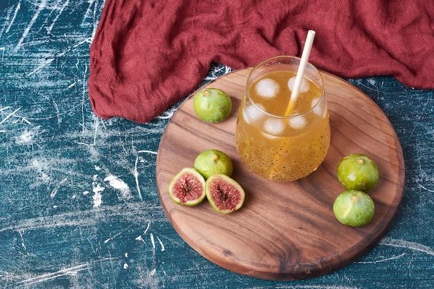 파란색에 주스 한 잔과 함께 녹색 무화과.
