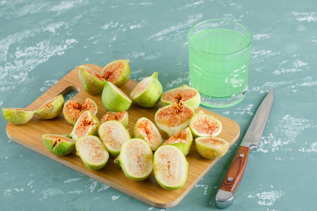 Green figs with drink, knife on plaster and cutting board, top view.